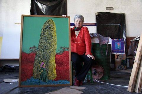 Marie-Josée à côté de son tableau au menhir, une oeuvre collective avec Odile Le Bras.