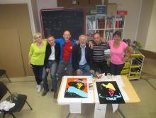 Le groupe des peintres nizonnais devant les deux tableaux réalisés, une Mamm-Gozh et un portrait de d'Artagnan